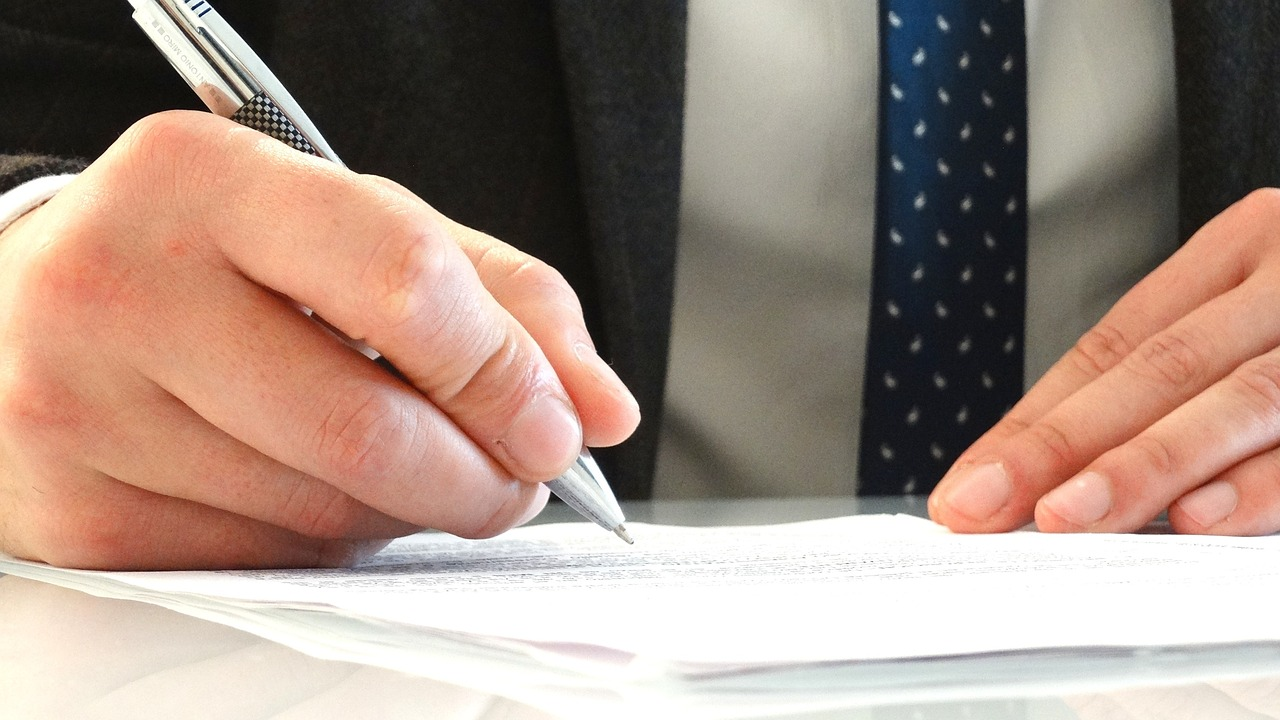 Man in a suit writing on a form