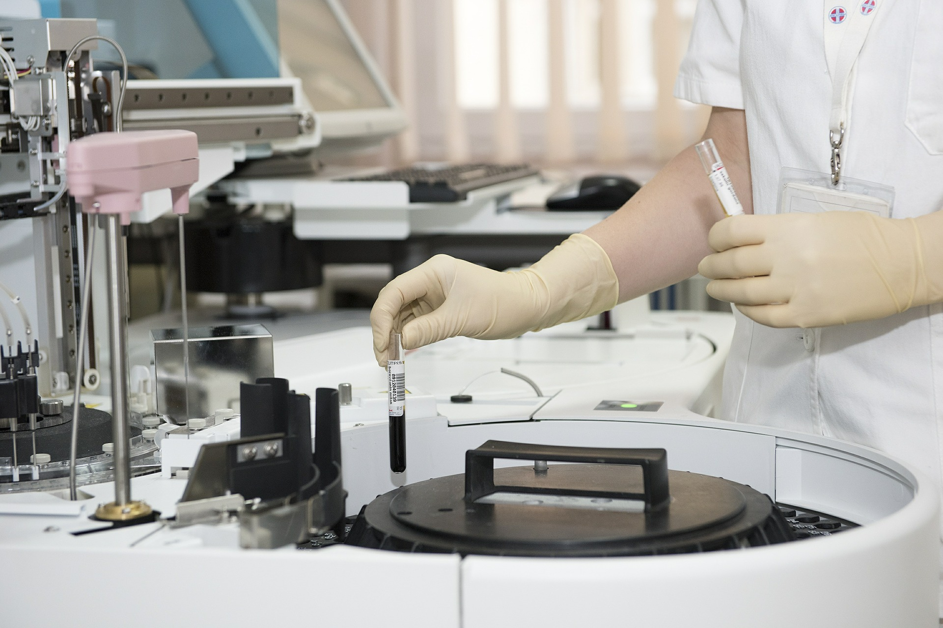 A lab assistant places test tubes containing liquid into a centrifuge