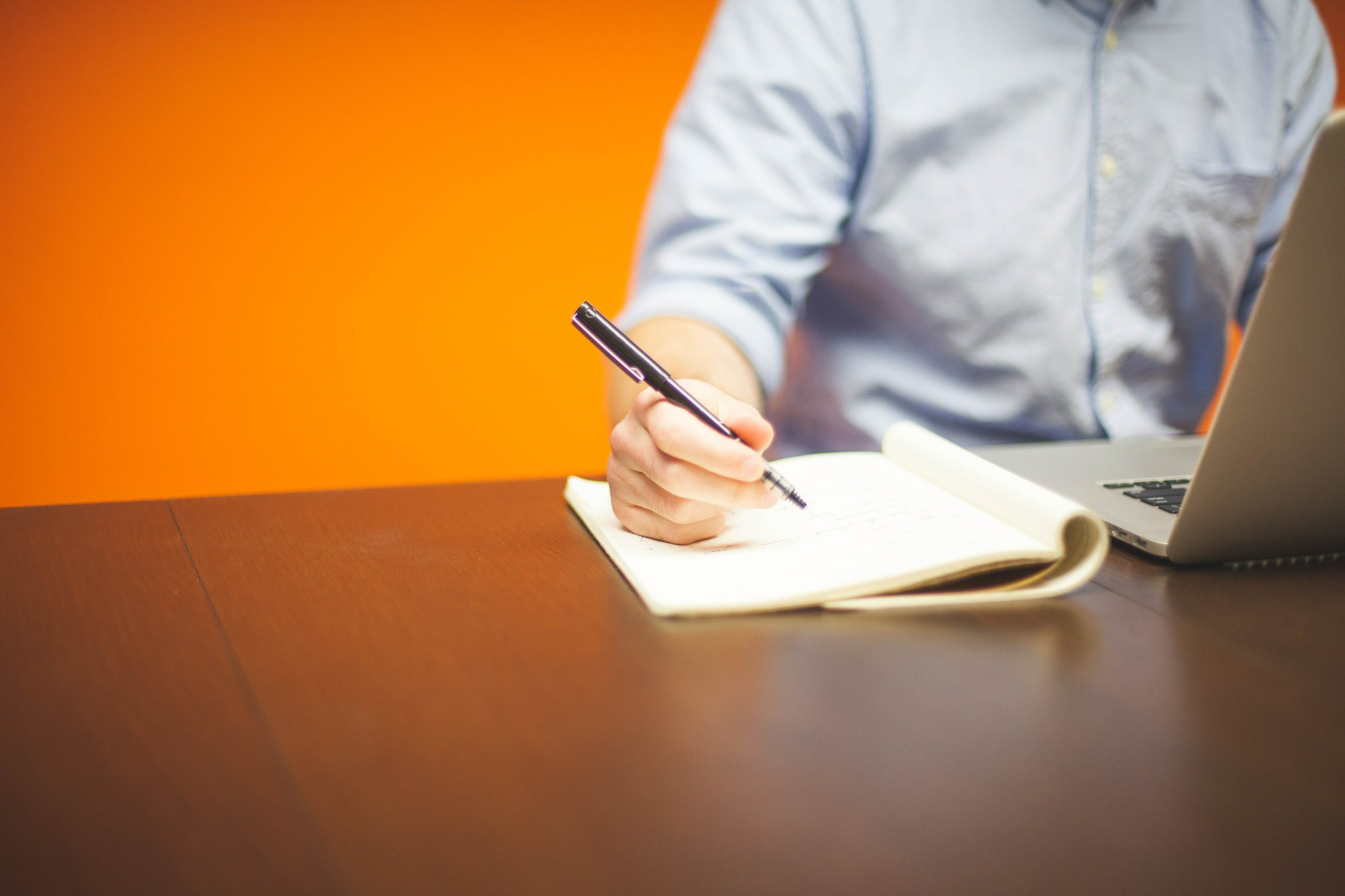 A person writes notes on a notepad whilst reading something off a laptop in a brightly painted room