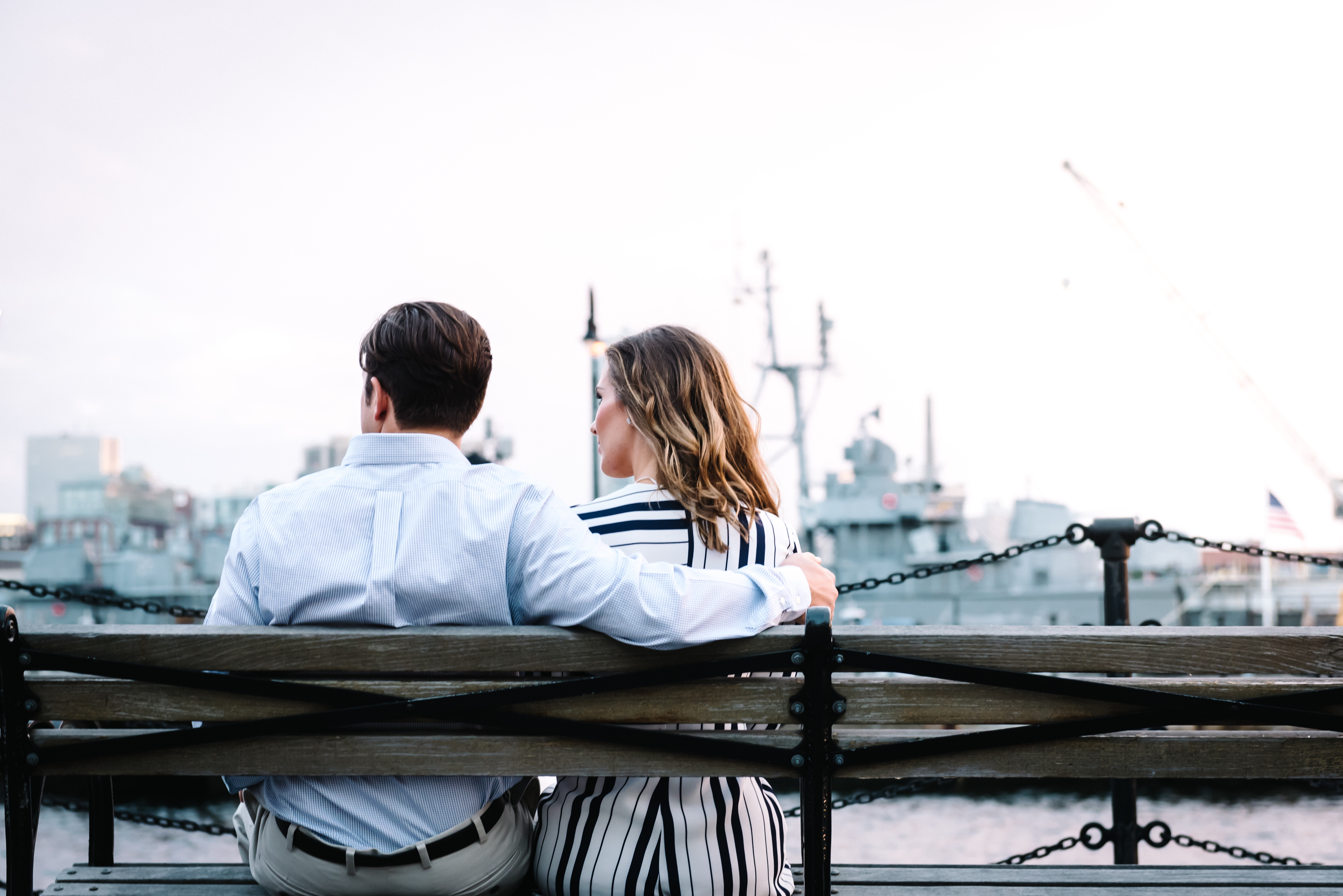 Two people sat by a harbour on a bench