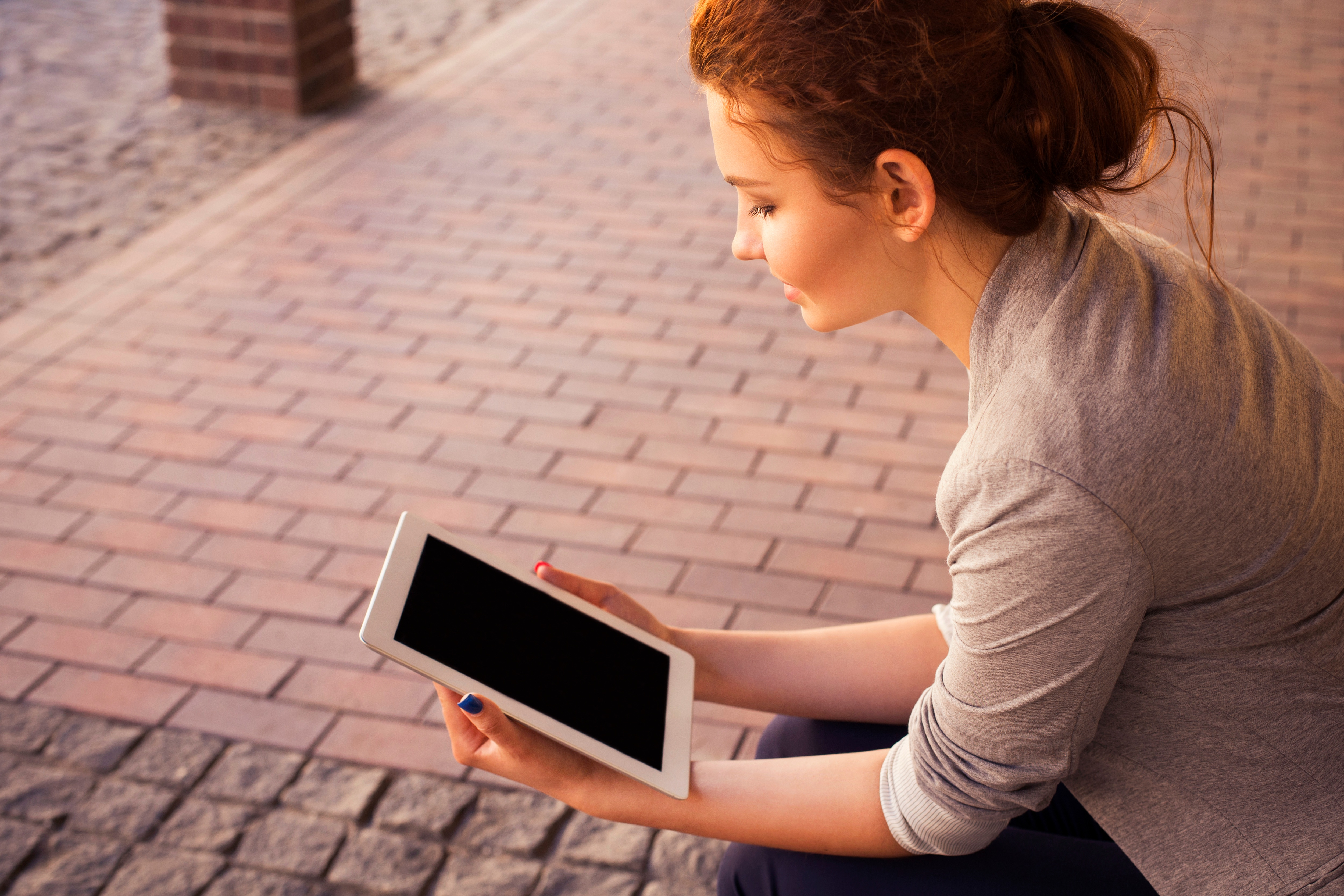 A young lady reads her tablet whilst sat on a brick road