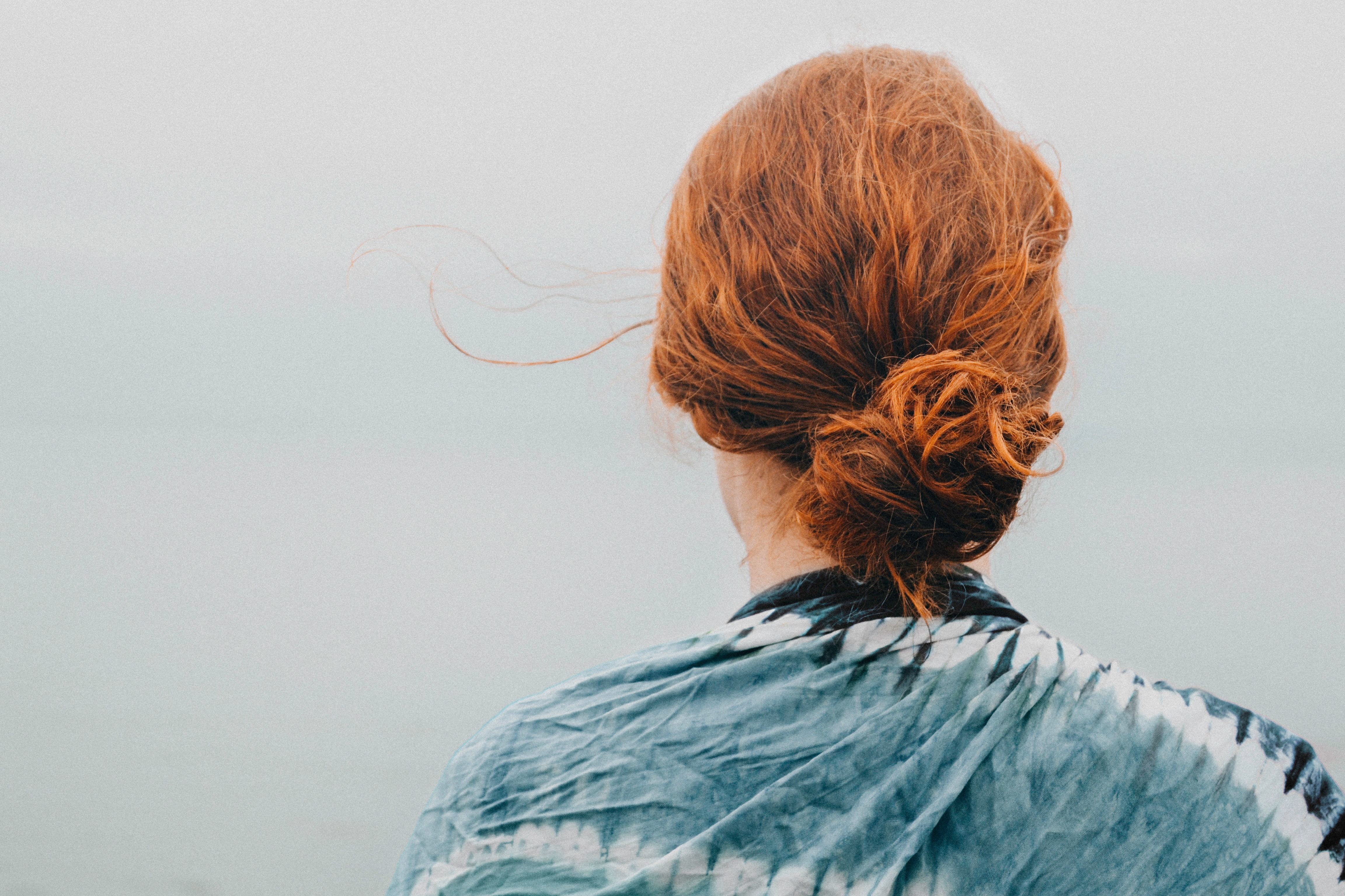 A woman with red hair looks out over a misty vista