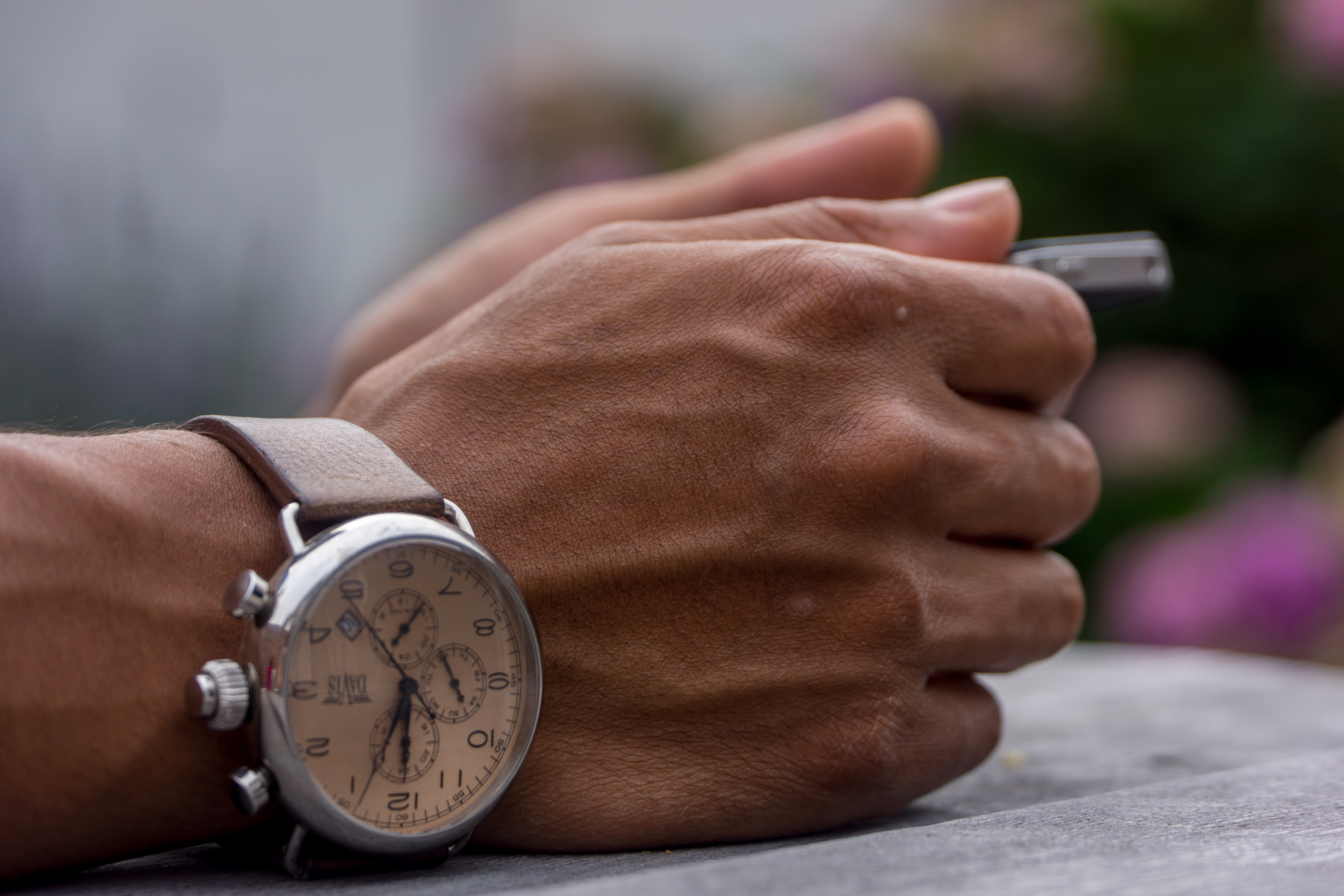 someones hands restingon a table holding a pen with a silver watch with brown leather strap on his wrist